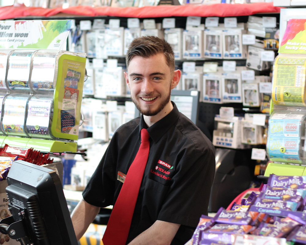 Smiling male staff member in Spar store